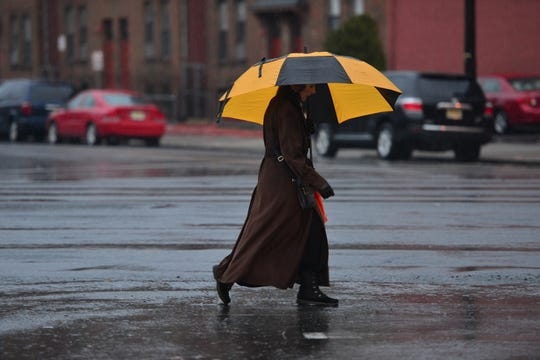 A woman uses an umbrella to shield herself from the rain as she walks toward to the Essex St Train Station in Hackensack on Friday March 22, 2019.