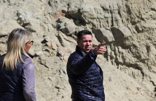 U.S. Rep. Ben Ray Lujan points to berms of debris piled alongside the Farmers Mutual Ditch, Friday, March 22, 2019, at the base of Harper Hill.