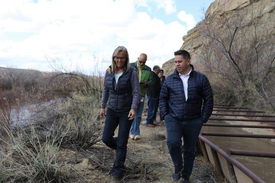 Danene Sherwood and U.S. Rep. Ben Ray Lujan walk along a metal flume transporting water in Farmers Mutual Ditch.