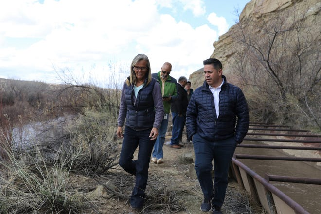 Danene Sherwood and U.S. Rep. Ben Ray Lujan walk along a metal flume transporting water in Farmers Mutual Ditch.
