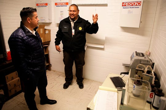 U.S. Rep. Ben Ray Luján, D-N.M., left, speaks to Sgt. Ed Cohoe, right, about using equipment to measure an inmate's Blood Alcohol Content in a room at the Shiprock Police Department Friday.