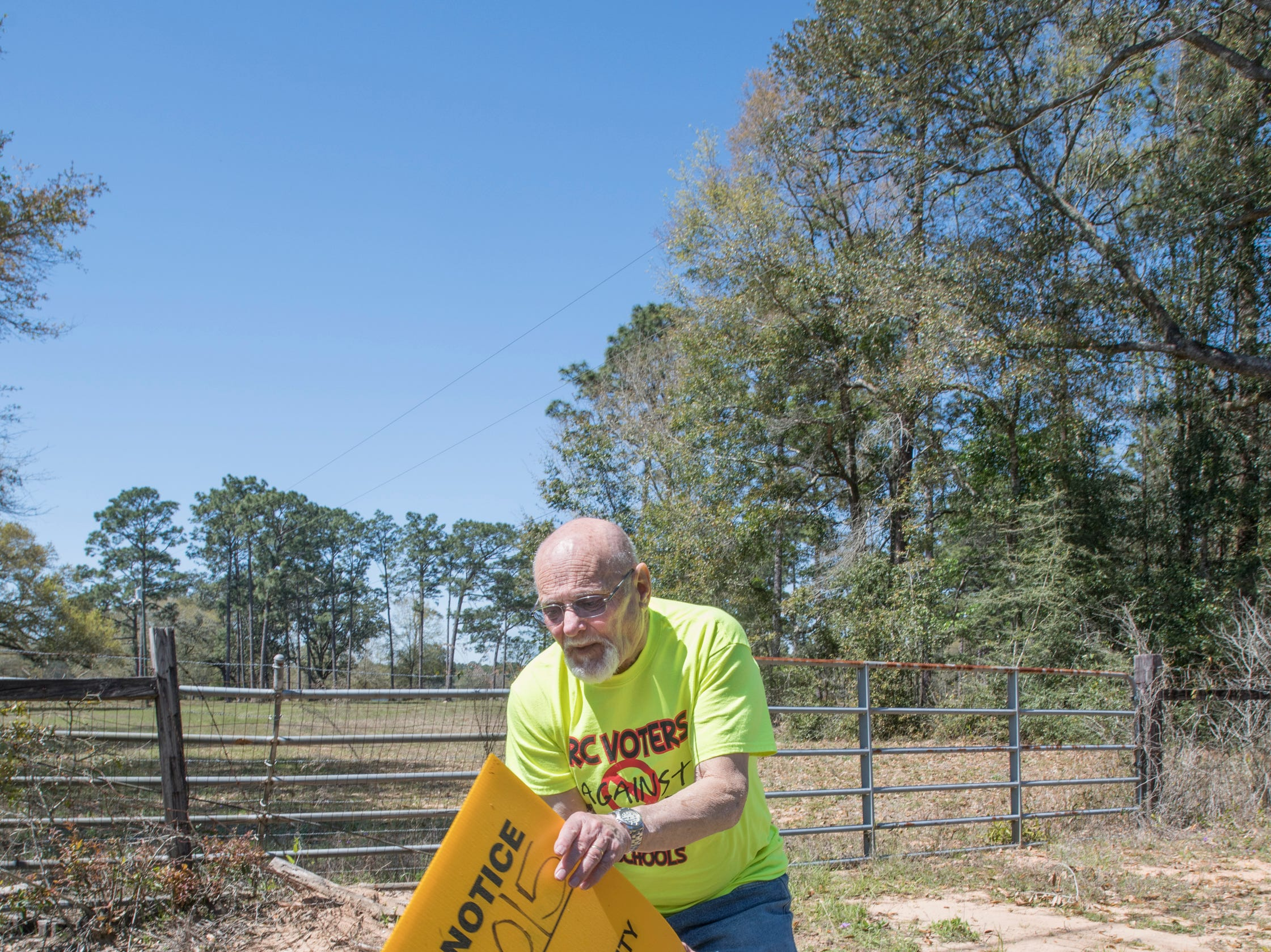 Phil Hoffman, the president of Santa Rosa Voters Against Overcrowded Roads and Schools, picks up a zoning meeting sign along the land where a 726-home subdivision along Woodbine Road is proposed in Pace on Friday, March 22, 2019.  Hoffman explains that the county should reinstate an impact fee so that the proposed subdivision, that would substantially worsen traffic that is already bad, would help fund widening of street.