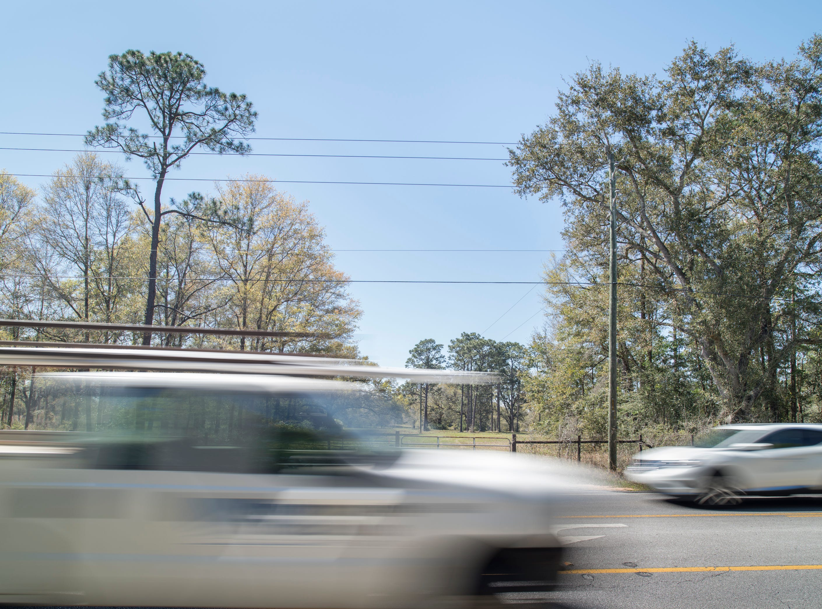 Vehicles drive past the land where a 726-home subdivision along Woodbine Road is proposed in Pace on Friday, March 22, 2019.  Phil Hoffman, the president of Santa Rosa Voters Against Overcrowded Roads and Schools, explains that the county should reinstate an impact fee so that the proposed subdivision, that would substantially worsen traffic that is already bad, would help fund widening of street.