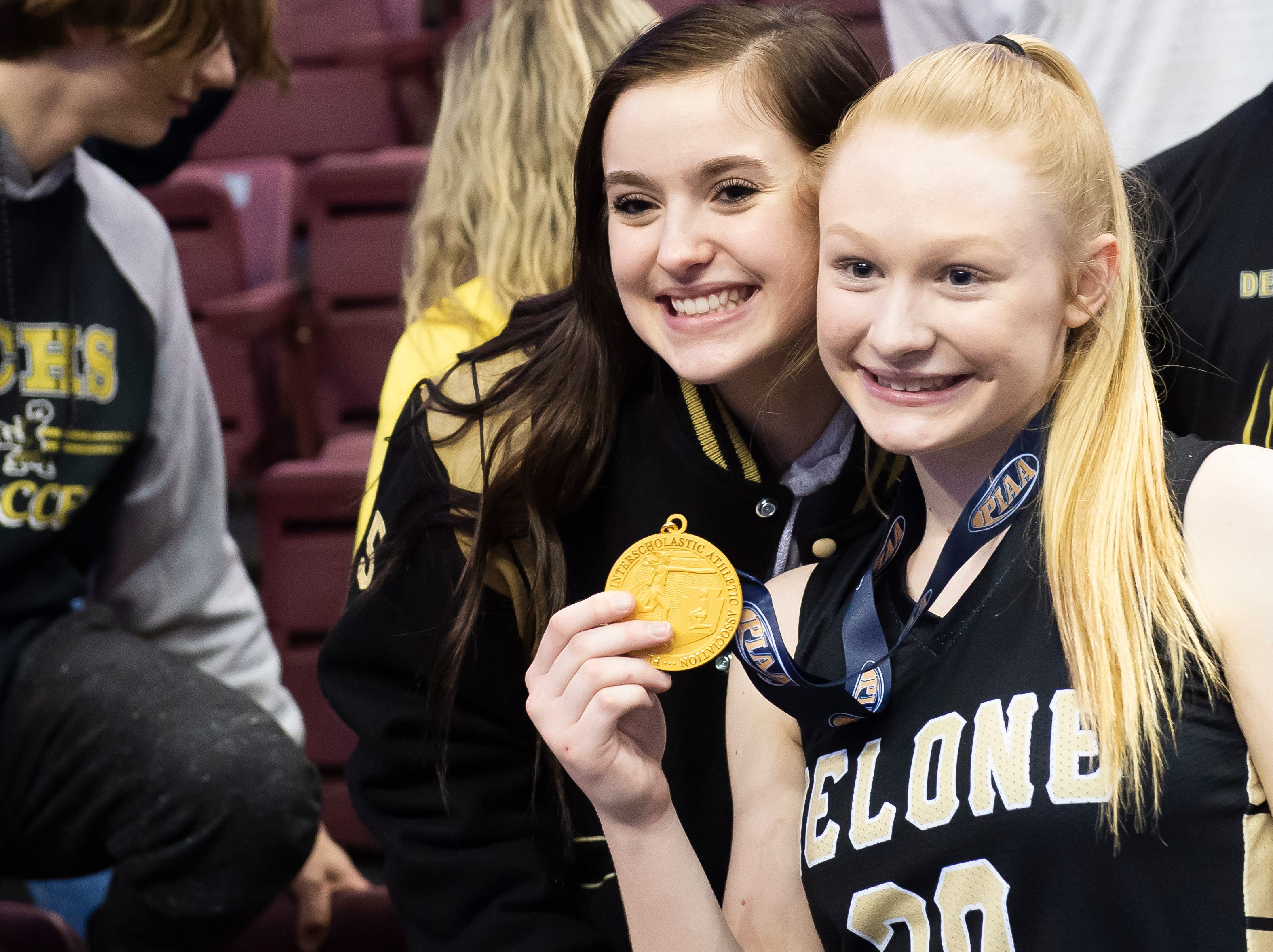 Delone Catholic's Brooke Lawyer holds up her gold medal as she poses for a photo with Emily Snyder after the Squirettes defeated Dunmore in the PIAA 3A championship game at the Giant Center in Hershey on Thursday, March 21, 2019. Delone won 49-43.