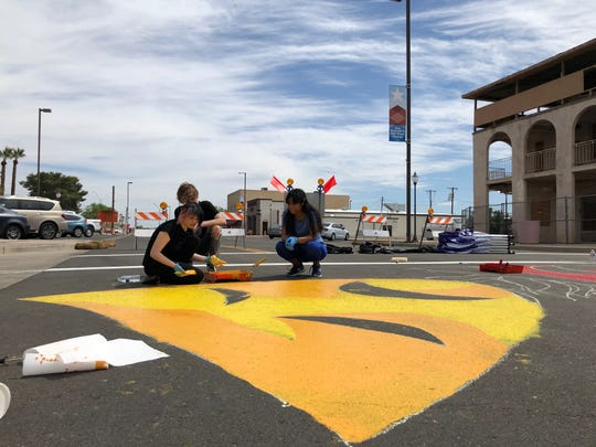 Students work on painting an Old Town Peoria intersection.