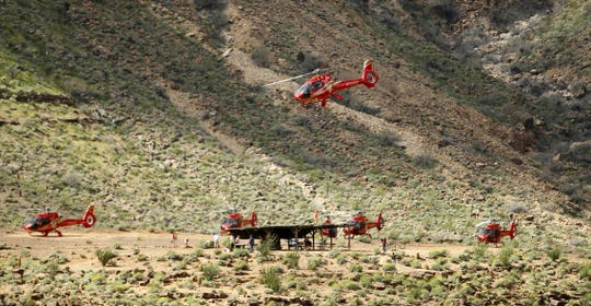 A Papillon Grand Canyon Helicopter flies in the western part of Grand Canyon National Park as others sit on landing pad on the Hualapai Reservation.