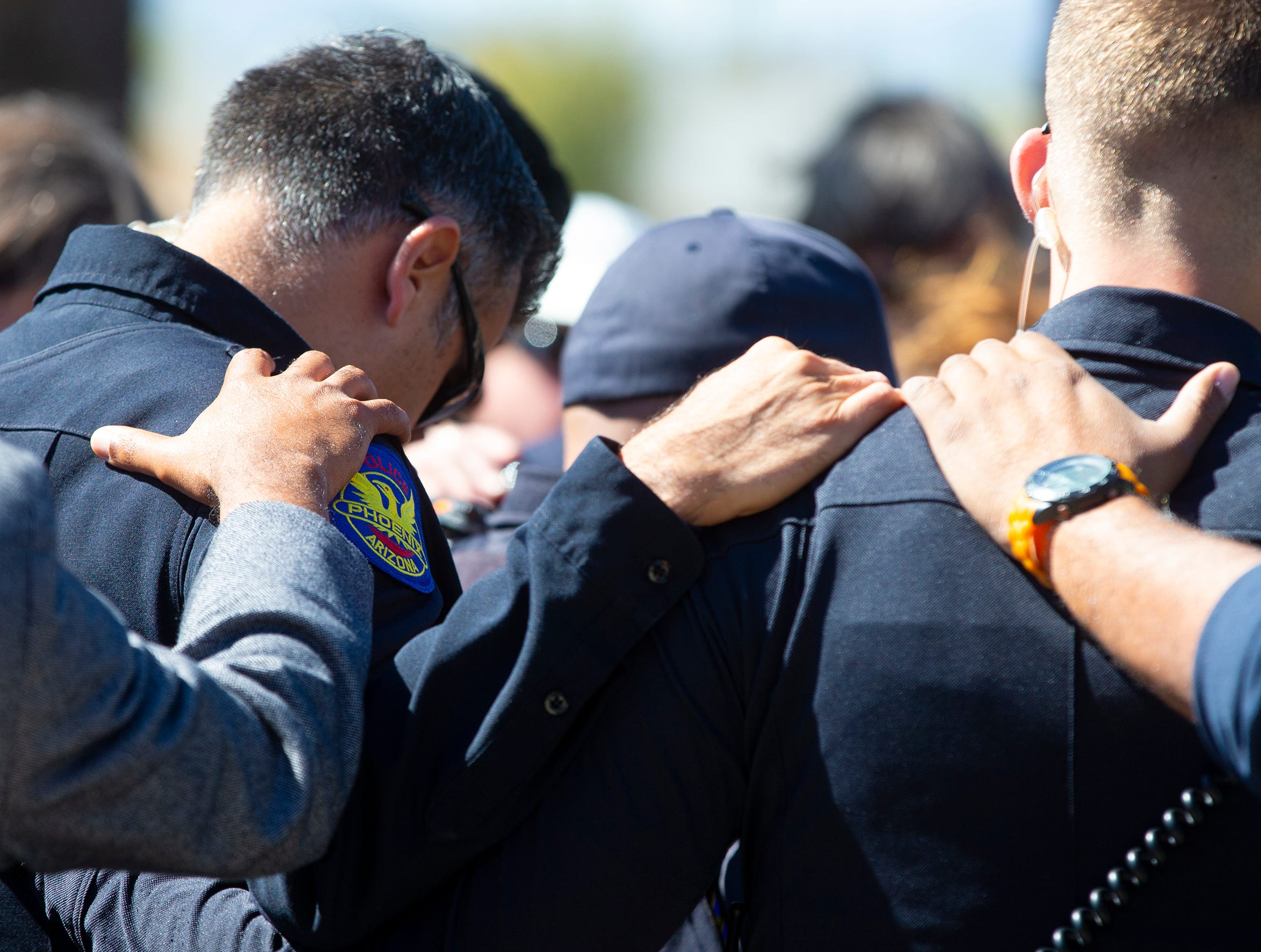 Pastor Ellis Ogles prays with officers March 22, 2019, during a gathering outside Phoenix Police Maryvale Precinct for Officer Paul Rutherford, who was killed in a crash March 21.