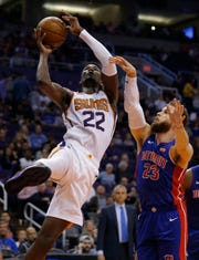 Suns center Deandre Ayton drives past Pistons forward Blake Griffin during a game on March 21.