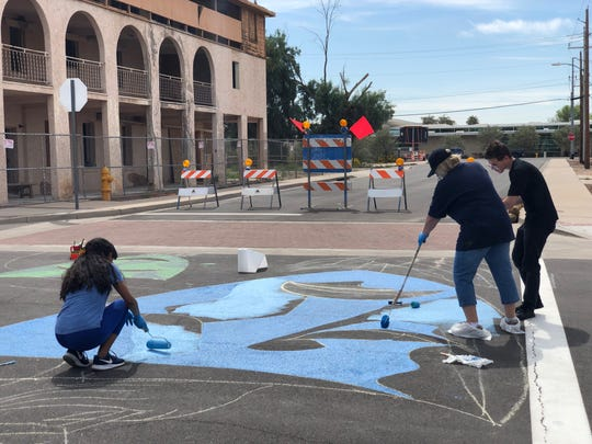 Connie Whitlock, WHAM Art Association executive director, helps high school students paint an Old Town Peoria intersection on Wednesday, March 20.