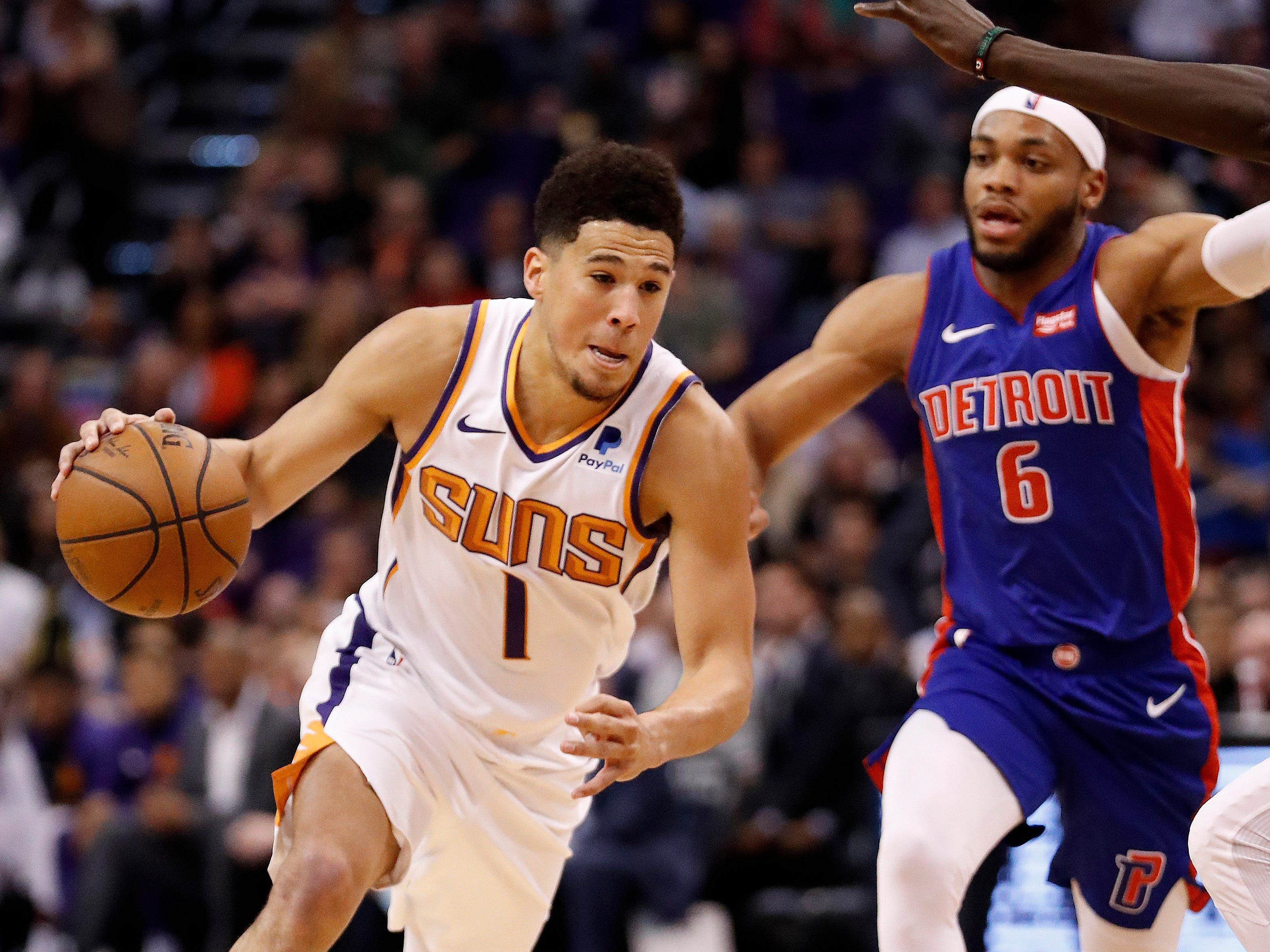 Phoenix Suns guard Devin Booker (1) drives as Detroit Pistons guard Bruce Brown (6) pursues during the second half of an NBA basketball game Thursday, March 21, 2019, in Phoenix.