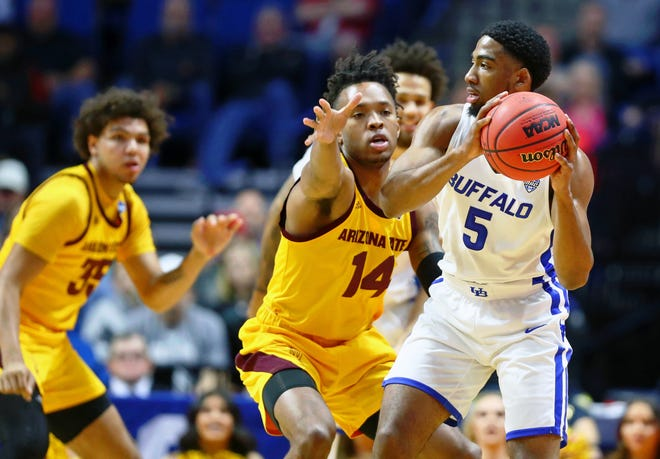 Buffalo Bulls guard CJ Massinburg (5) holds the ball while defended by Arizona State Sun Devils forward Kimani Lawrence (14) during the first half in the first round of the 2019 NCAA Tournament at BOK Center, March 22, 2019, in Tulsa, Okla.