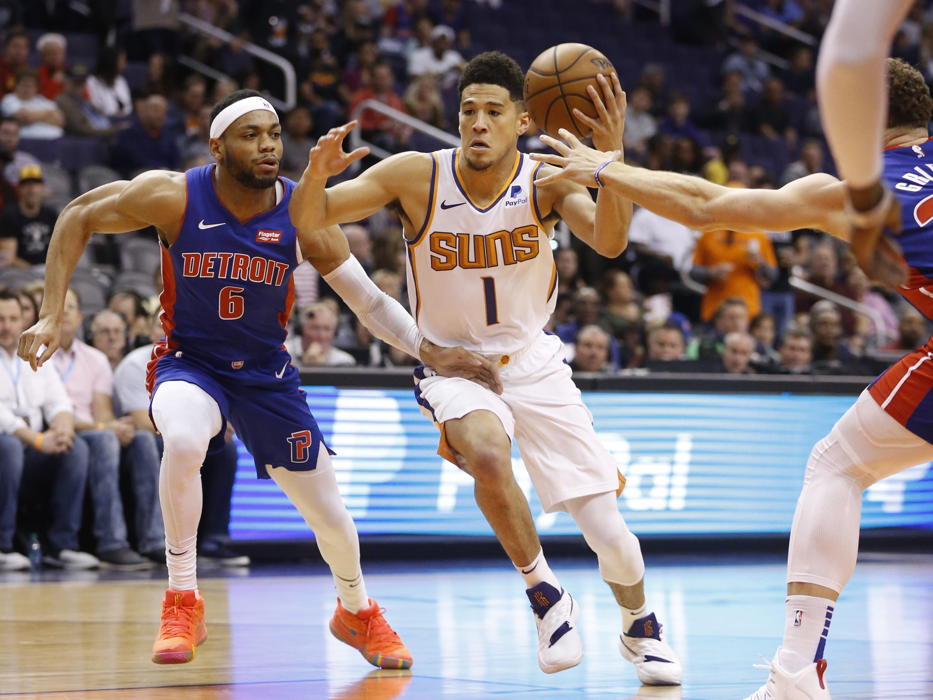 Suns' Devin Booker (1) dribbles into the lane against the Pistons' Bruce Brown (6) during the first half at the Talking Stick Resort Arena in Phoenix, Ariz. on March 21, 2019.