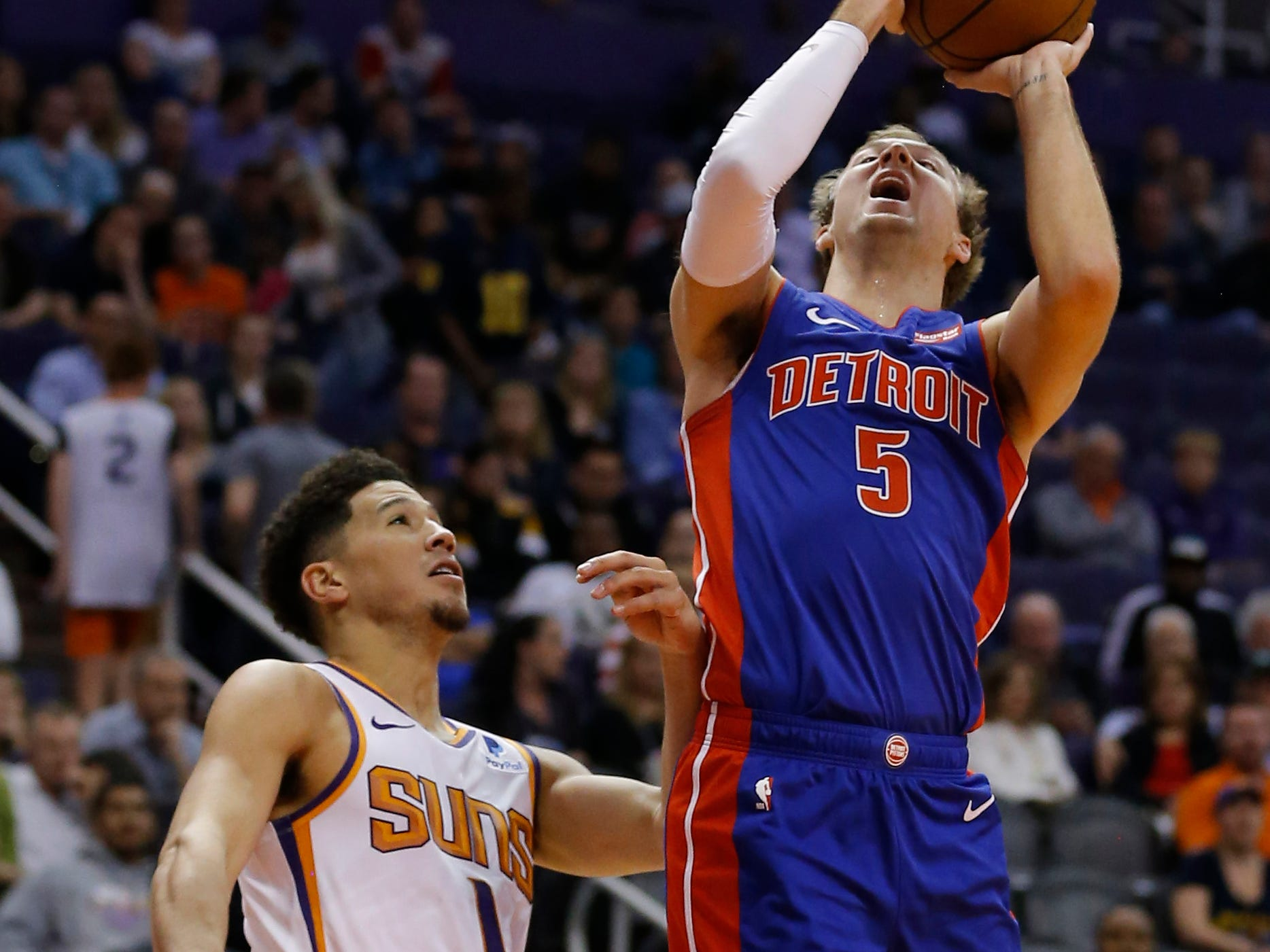 Mar 21, 2019; Phoenix, AZ, USA; Detroit Pistons guard Luke Kennard (5) gets fouled by Phoenix Suns guard Devin Booker (1) in the second half during an NBA basketball game at Talking Stick Resort Arena.