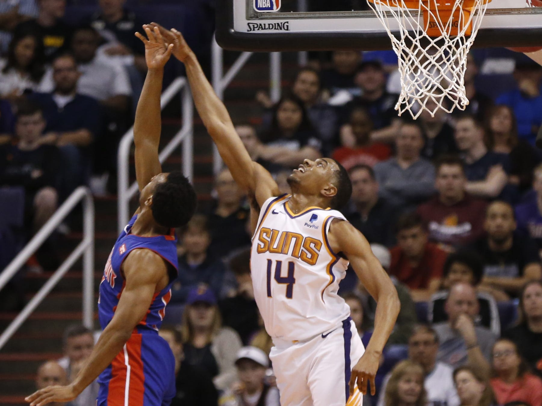 Suns' De'Anthony Melton (14) contests a layup against Pistons' Ish Smith during the first half at the Talking Stick Resort Arena in Phoenix, Ariz. on March 21, 2019.