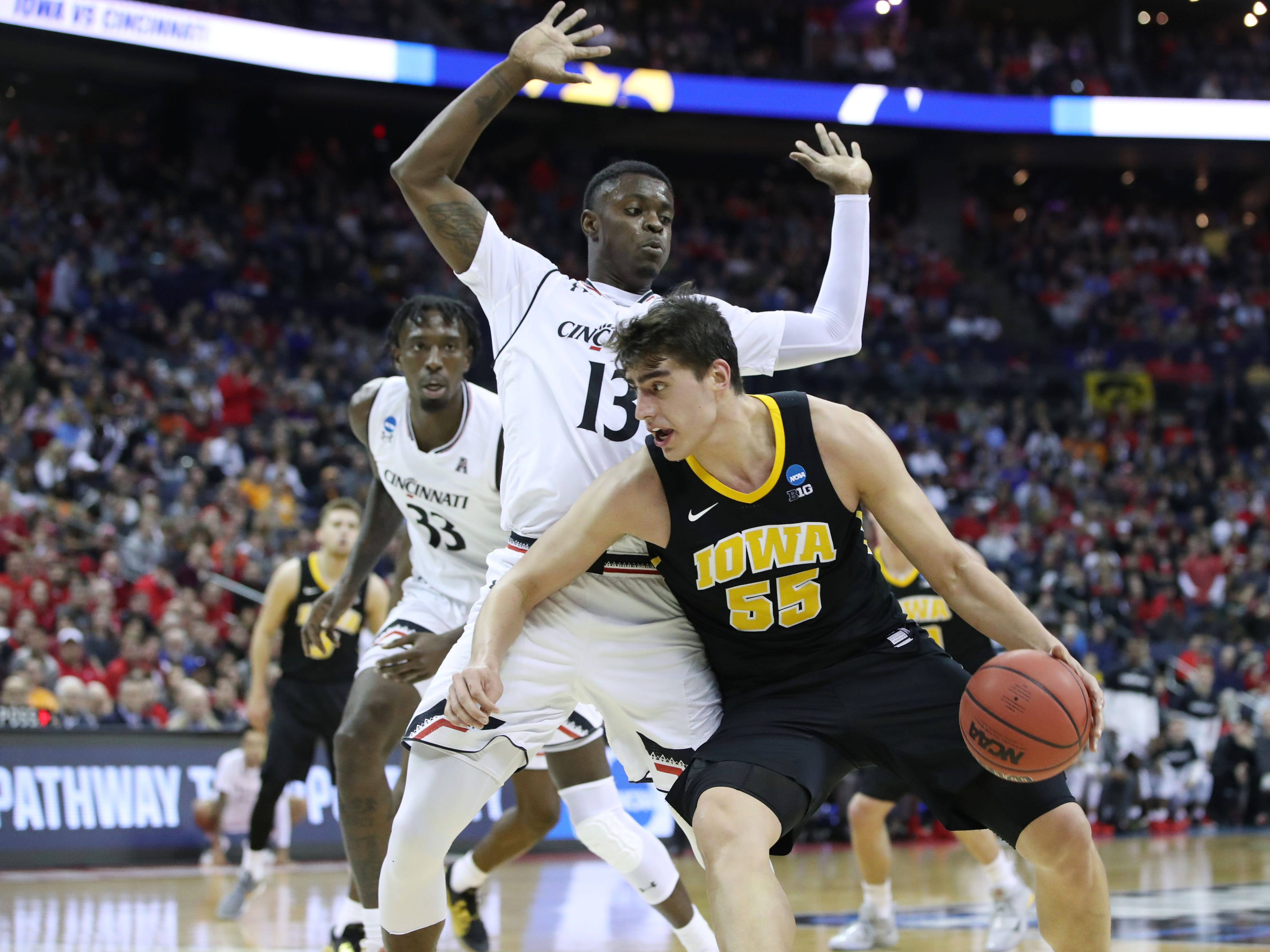 Iowa Hawkeyes forward Luka Garza (55) looks to move the ball defended by Cincinnati Bearcats forward Tre Scott (13) in the second half in the first round of the 2019 NCAA Tournament at Nationwide Arena on March 22, 2019.