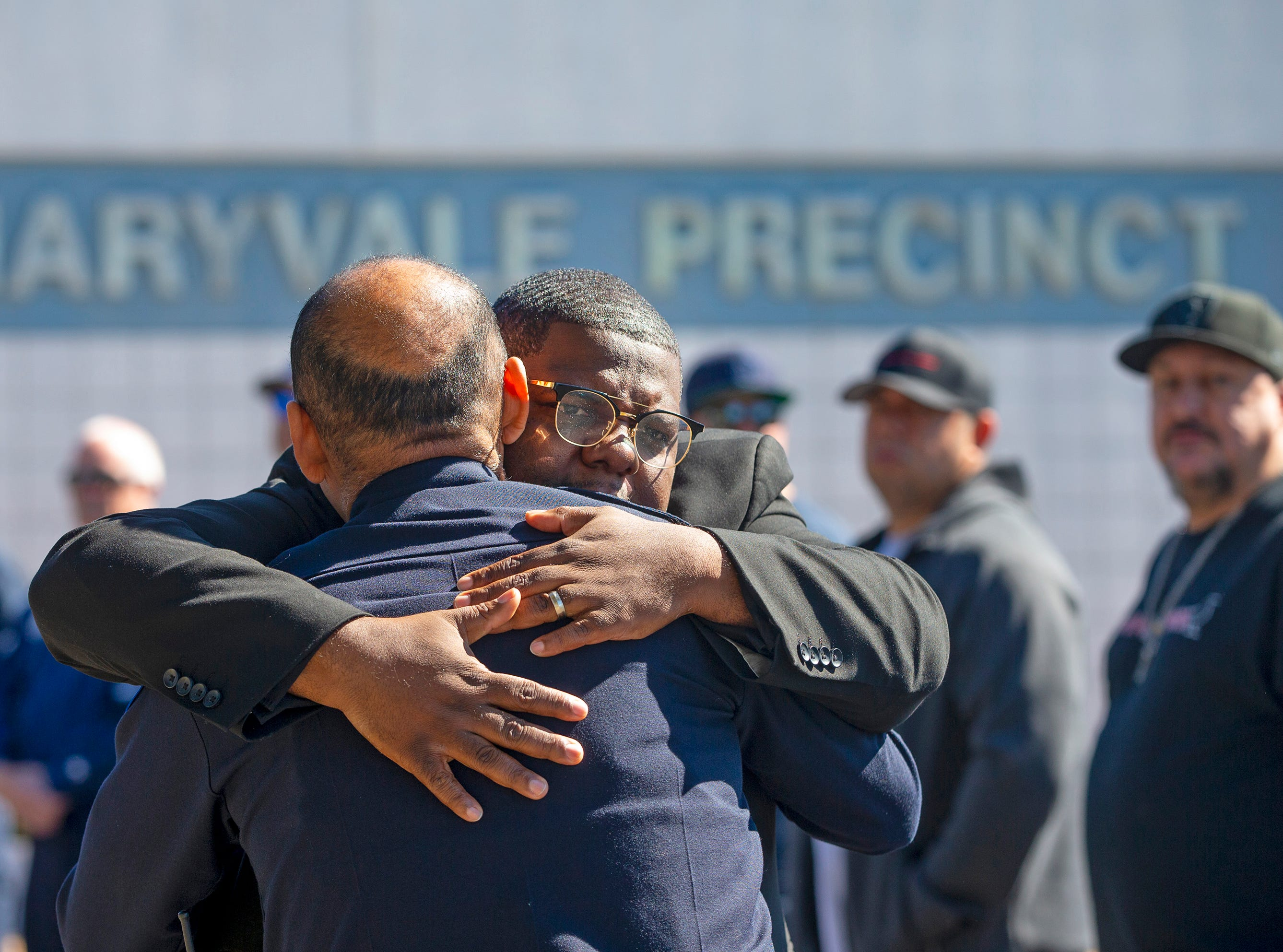 The Rev. Reginald D. Walton gives a hug to Lt. Mark Tovar Sr. March 22, 2019, during a prayer service outside Phoenix Police Maryvale Precinct for Officer Paul Rutherford, who was killed in a crash March 21.