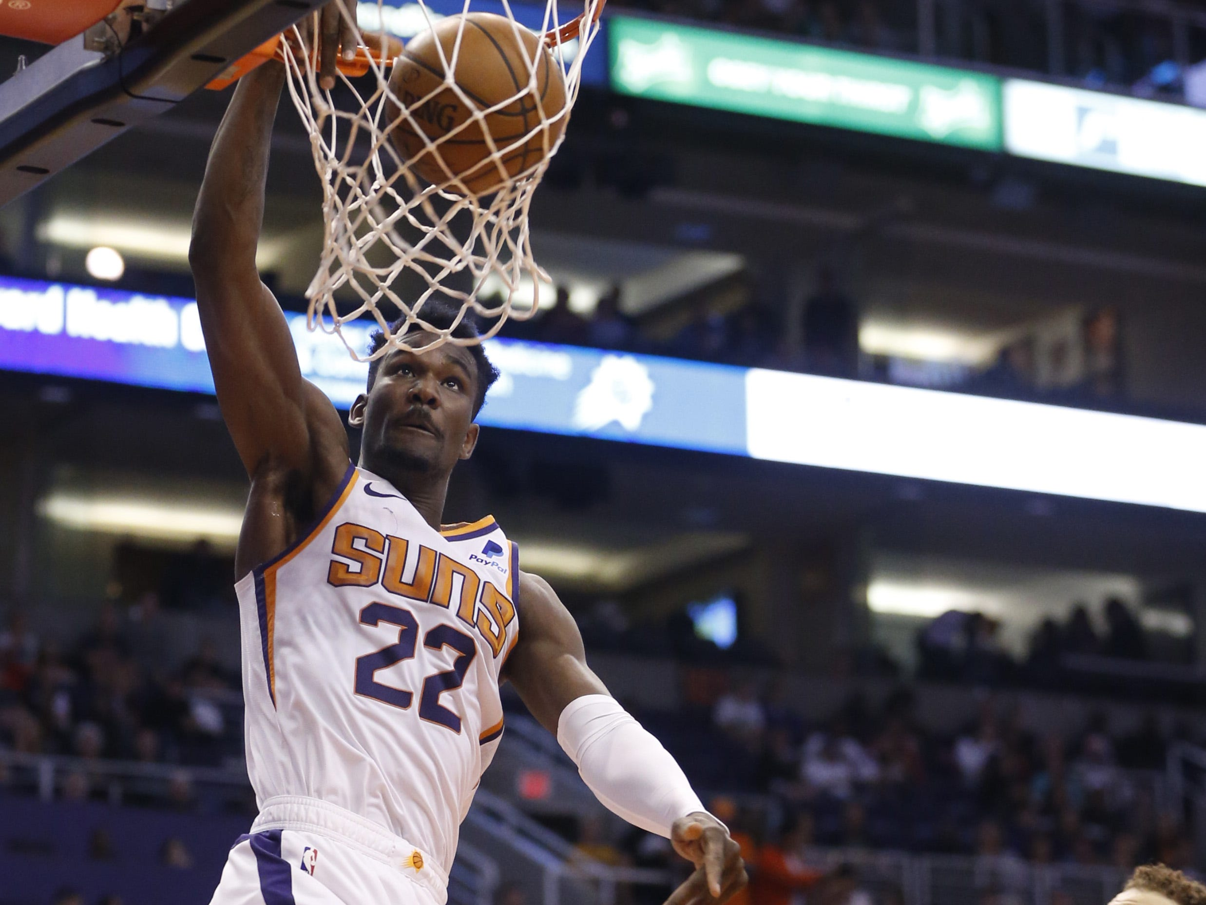 Suns' Deandre Ayton (22) dunks against the Pistons' Blake Griffin (23) during the first half at the Talking Stick Resort Arena in Phoenix, Ariz. on March 21, 2019.
