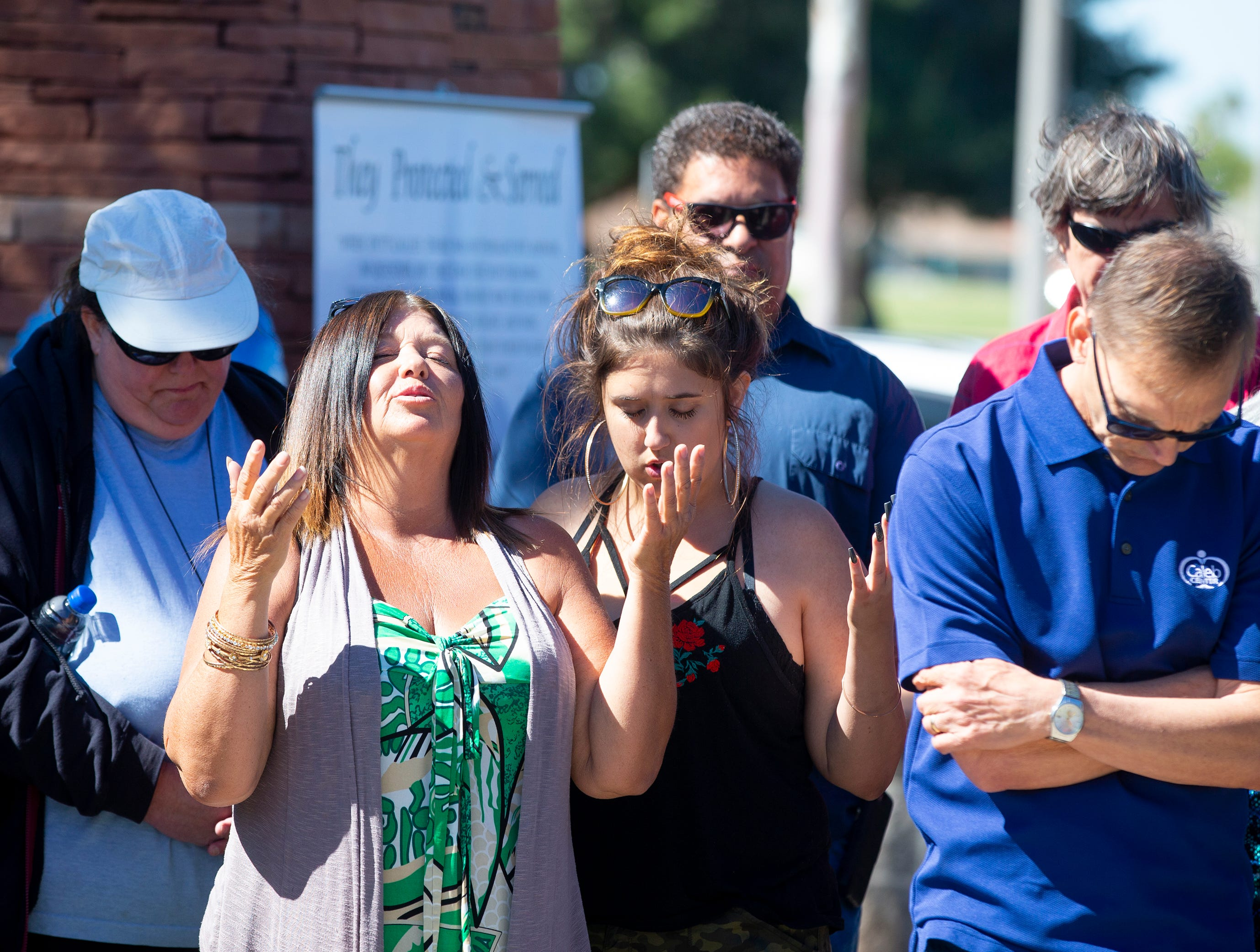 Holly Alsup of Phoenix prays March 22, 2019, during a gathering outside Phoenix Police Maryvale Precinct for Officer Paul Rutherford, who was killed in a crash March 21.