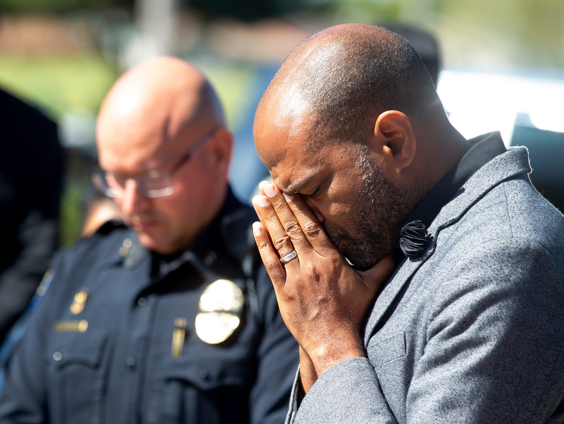 Pastor Ellis Ogles  prays during a gathering March 22, 2019, outside Phoenix Police Maryvale Precinct for Officer Paul Rutherford, who was killed in a crash March 21.