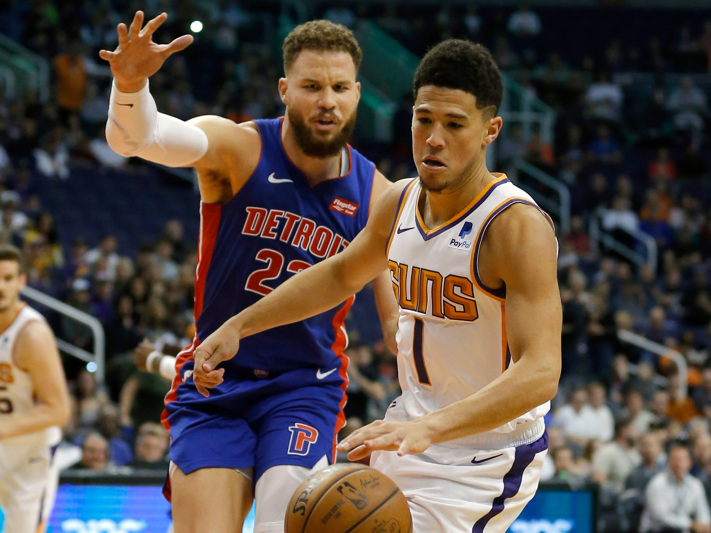 Mar 21, 2019; Phoenix, AZ, USA; Phoenix Suns guard Devin Booker (1) shields the ball from Detroit Pistons forward Blake Griffin (23) in the first half during an NBA basketball game at Talking Stick Resort Arena.
