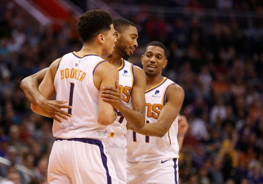 Mikal Bridges (25) and De'Anthony Melton (14) grab Devin Booker (1) after Booker was called for a technical foul during the second half of a game against the Pistons at Talking Stick Resort Arena.