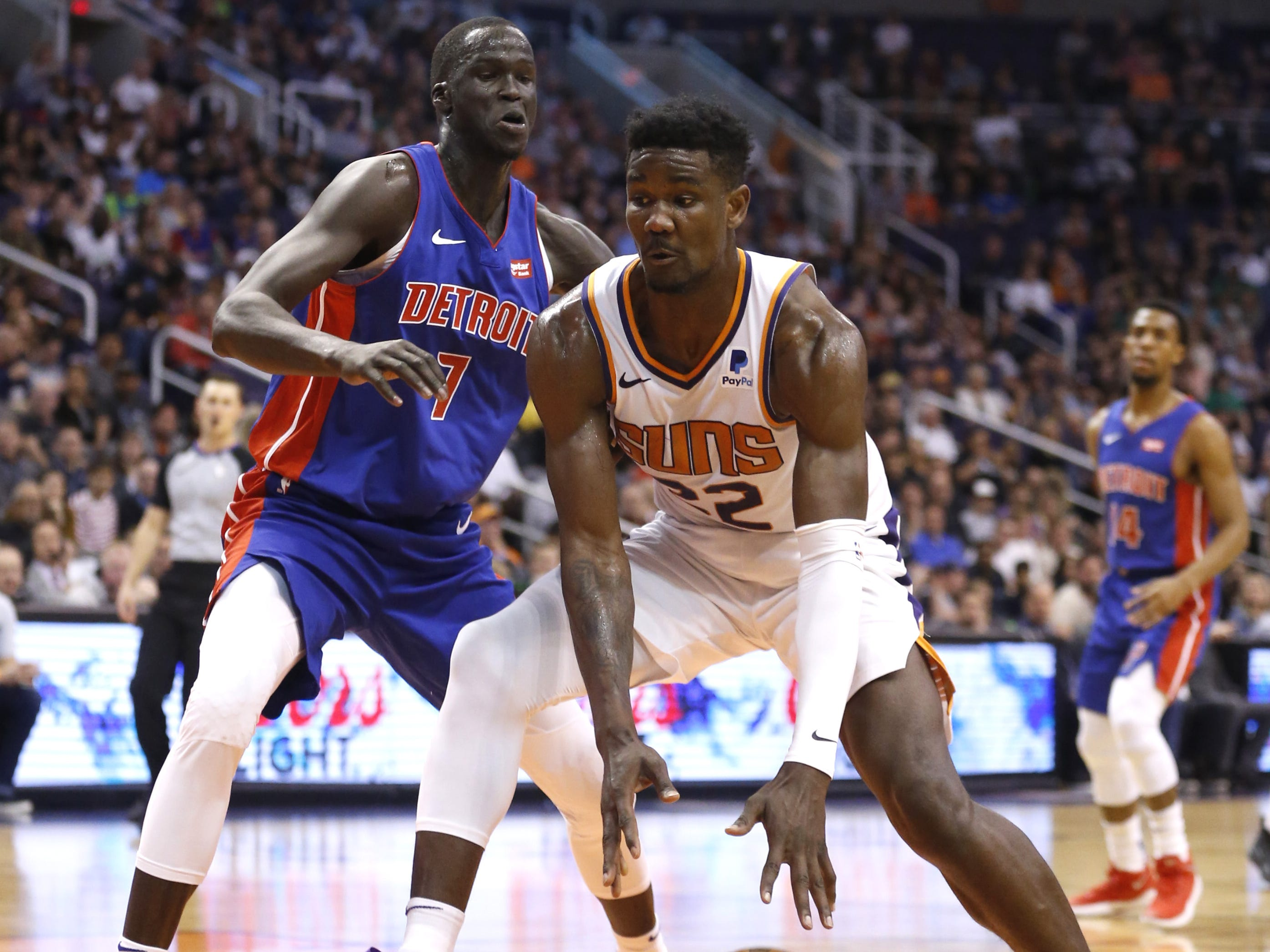 Suns' Deandre Ayton (22) dribbles into the defense of Pistons' Then Maker (7) during the first half at the Talking Stick Resort Arena in Phoenix, Ariz. on March 21, 2019.