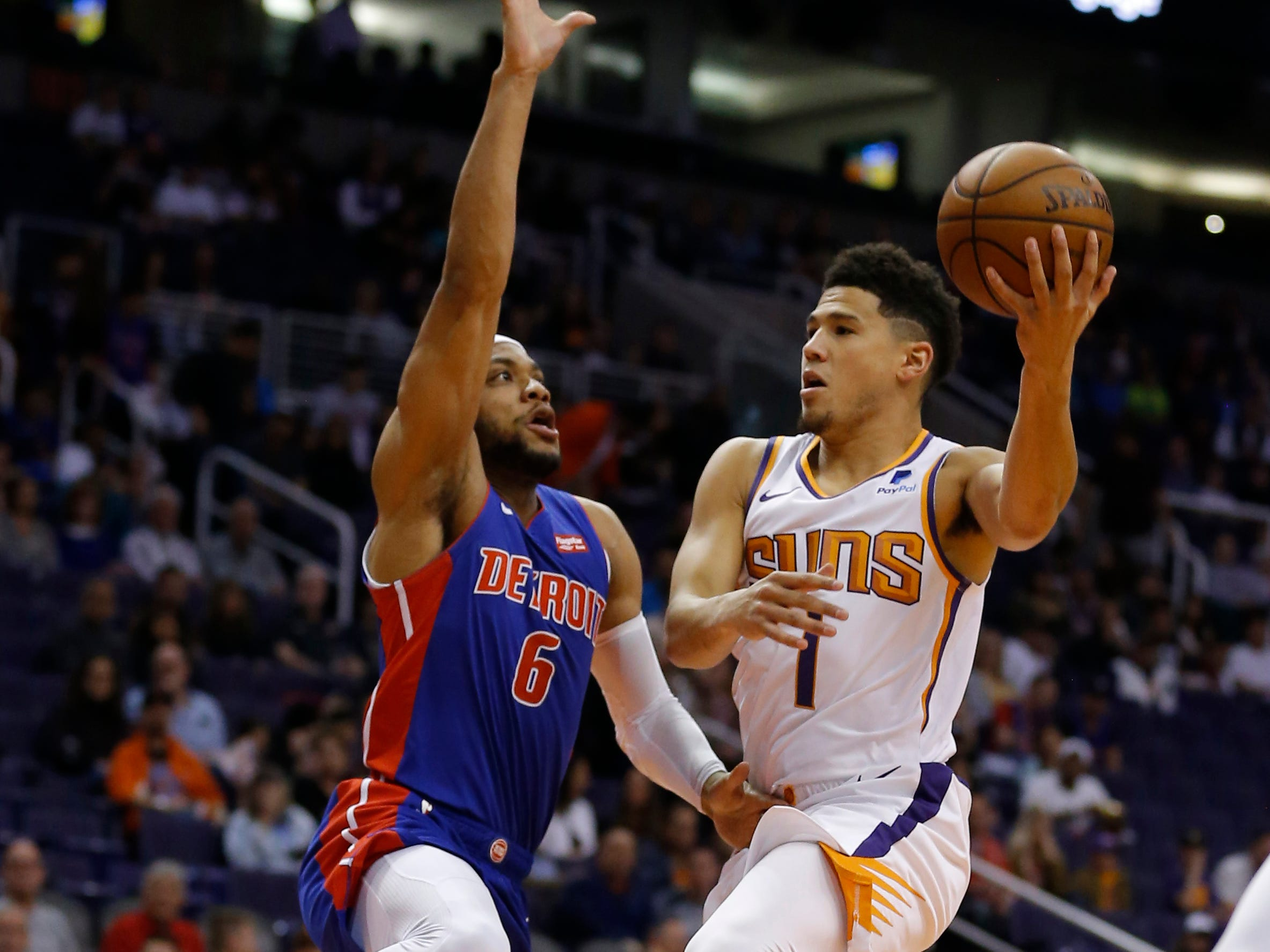 Mar 21, 2019; Phoenix, AZ, USA; Phoenix Suns guard Devin Booker (1) drives on Detroit Pistons guard Bruce Brown (6) in the first half during an NBA basketball game at Talking Stick Resort Arena.