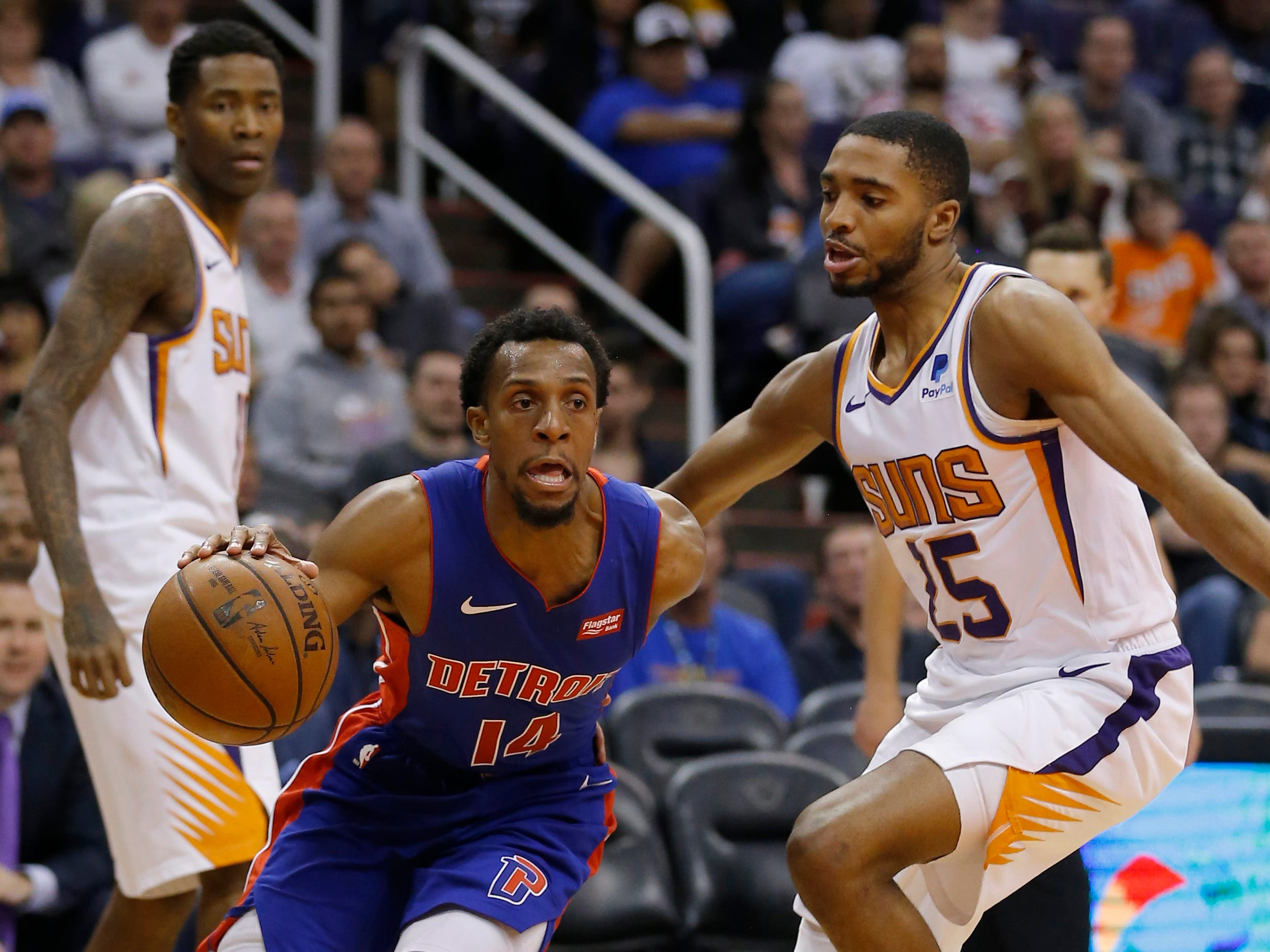 Mar 21, 2019; Phoenix, AZ, USA; Detroit Pistons guard Ish Smith (14) drives past Phoenix Suns forward Mikal Bridges (25) in the second half during an NBA basketball game at Talking Stick Resort Arena.
