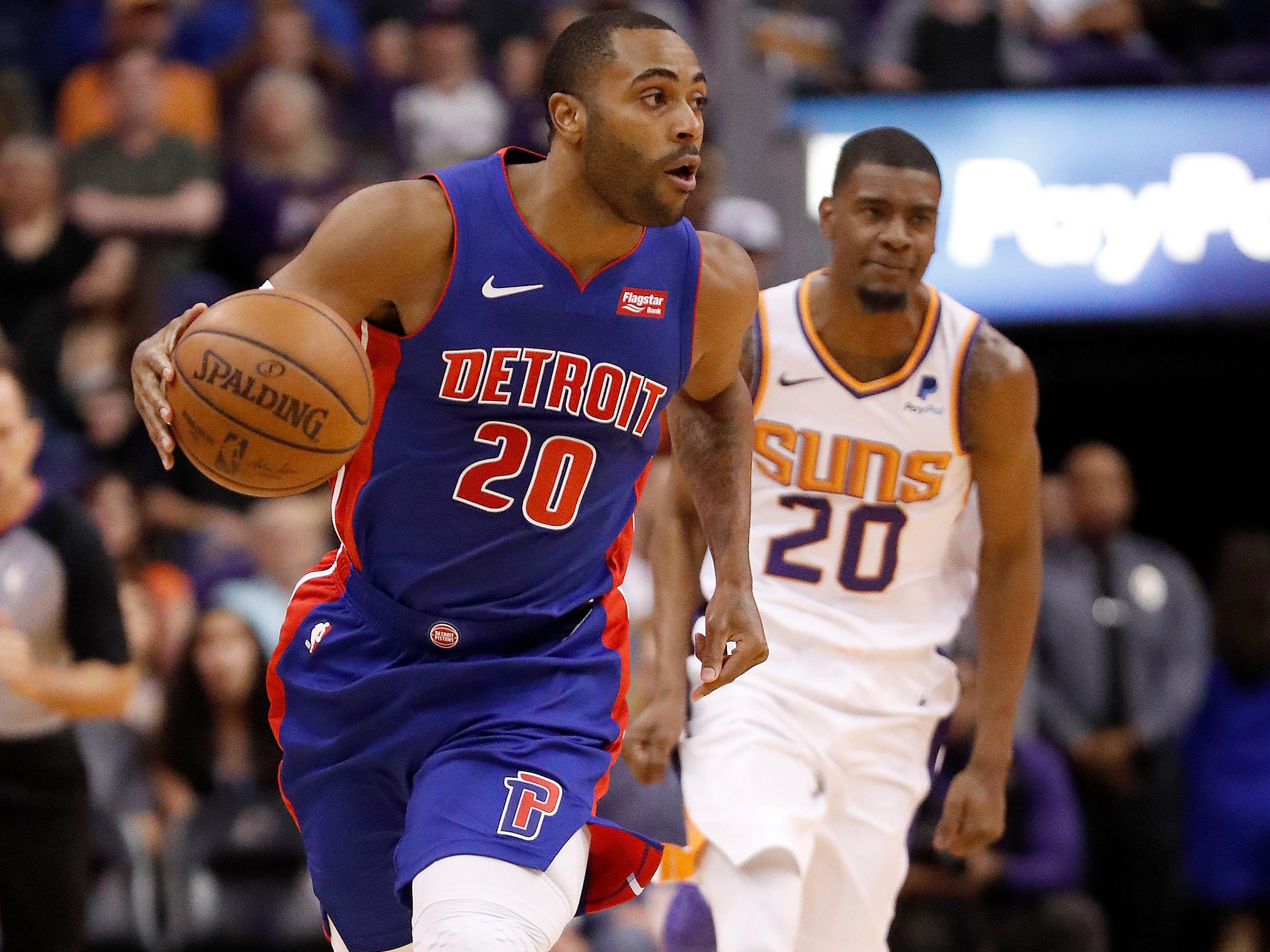 Detroit Pistons guard Wayne Ellington (20) moves the ball up as Phoenix Suns forward Josh Jackson (20) trails during the first half of an NBA basketball game Thursday, March 21, 2019, in Phoenix.