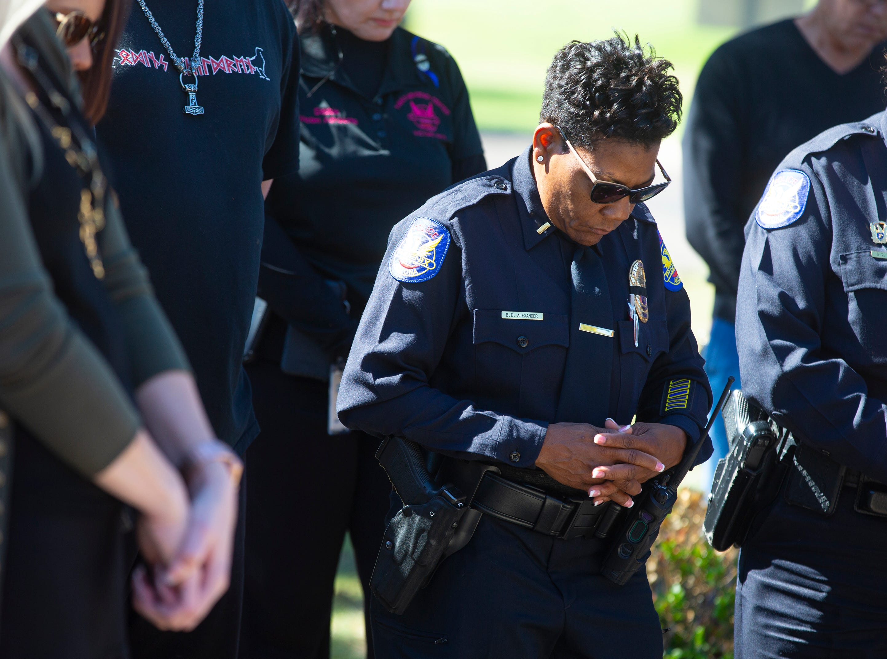 Lt. Barbara Alexander prays March 22, 2019, during a gathering outside Phoenix Police Maryvale Precinct for Officer Paul Rutherford, who was killed in a crash March 21.