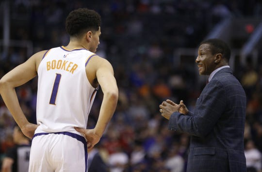 Devin Booker (1) talks with Pistons coach Dwane Casey during the second half of a game at Talking Stick Resort Arena.