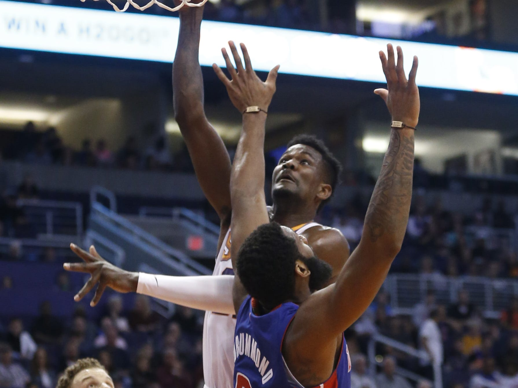 Suns' Deandre Ayton (22) scores against Pistons' Andre Drummond (0) during the first half at the Talking Stick Resort Arena in Phoenix, Ariz. on March 21, 2019.