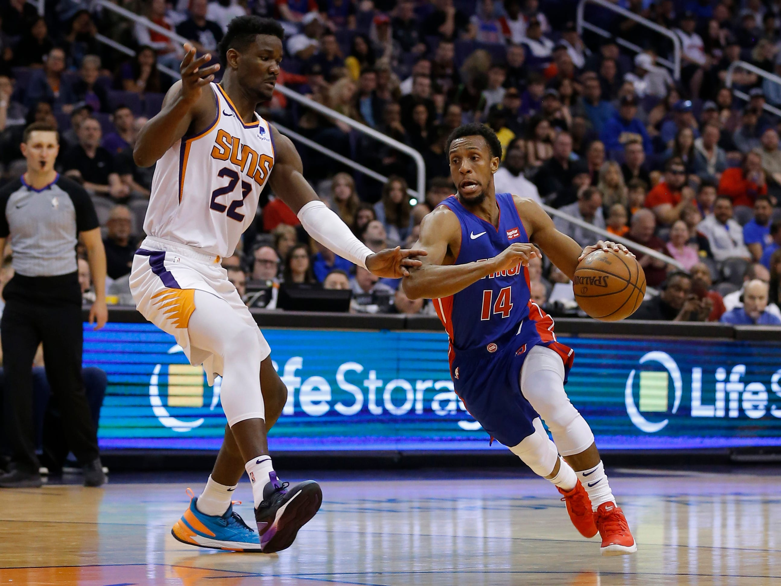 Mar 21, 2019; Phoenix, AZ, USA; Detroit Pistons guard Ish Smith (14) drives past Phoenix Suns center Deandre Ayton (22) in the second half during an NBA basketball game at Talking Stick Resort Arena.