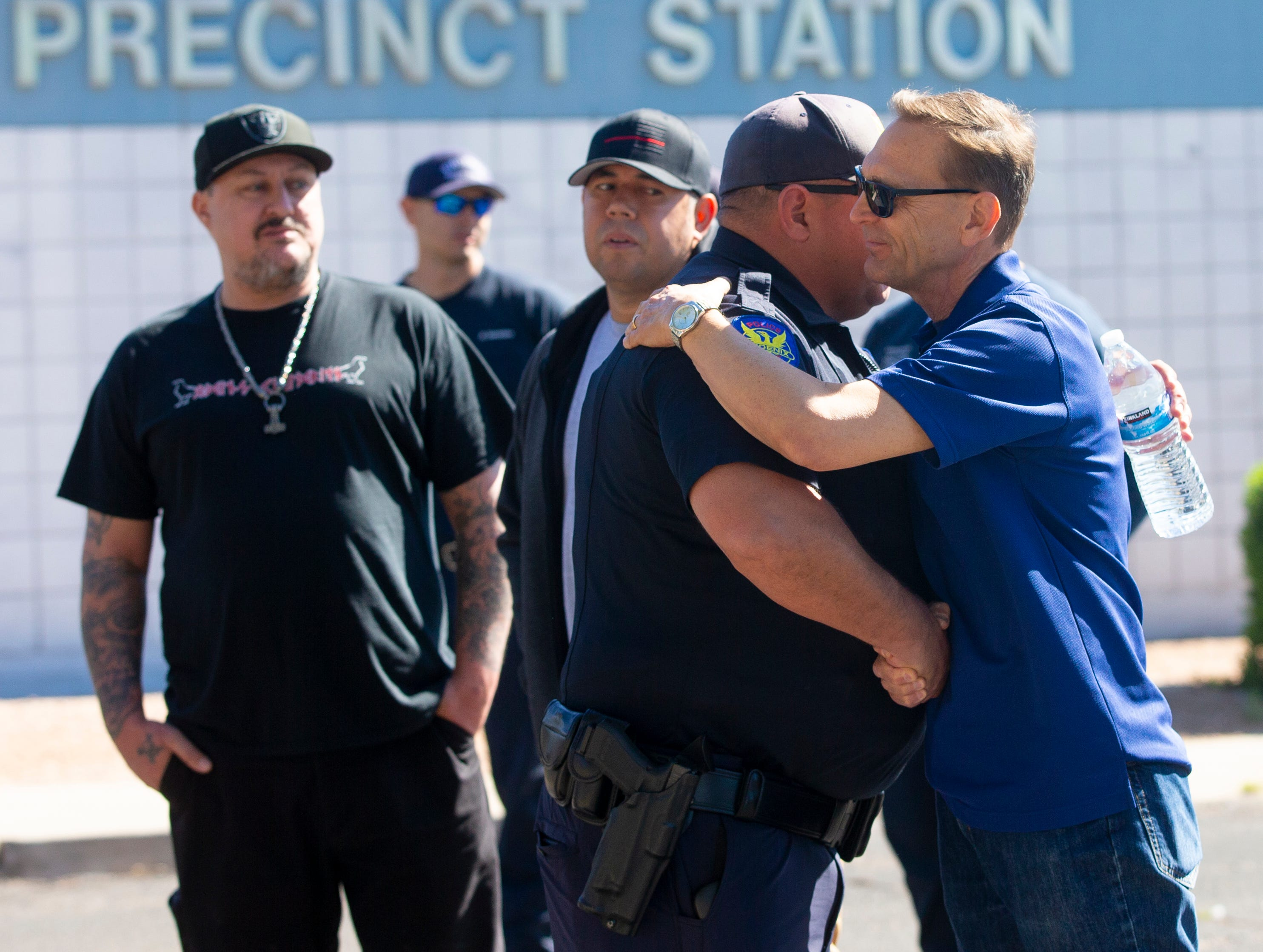 Officer Terry Laaker gives a hug to Pastor Dan Flemming March 22, 2019, during a prayer service outside Phoenix Police Maryvale Precinct for Officer Paul Rutherford, who was killed in a crash March 21.
