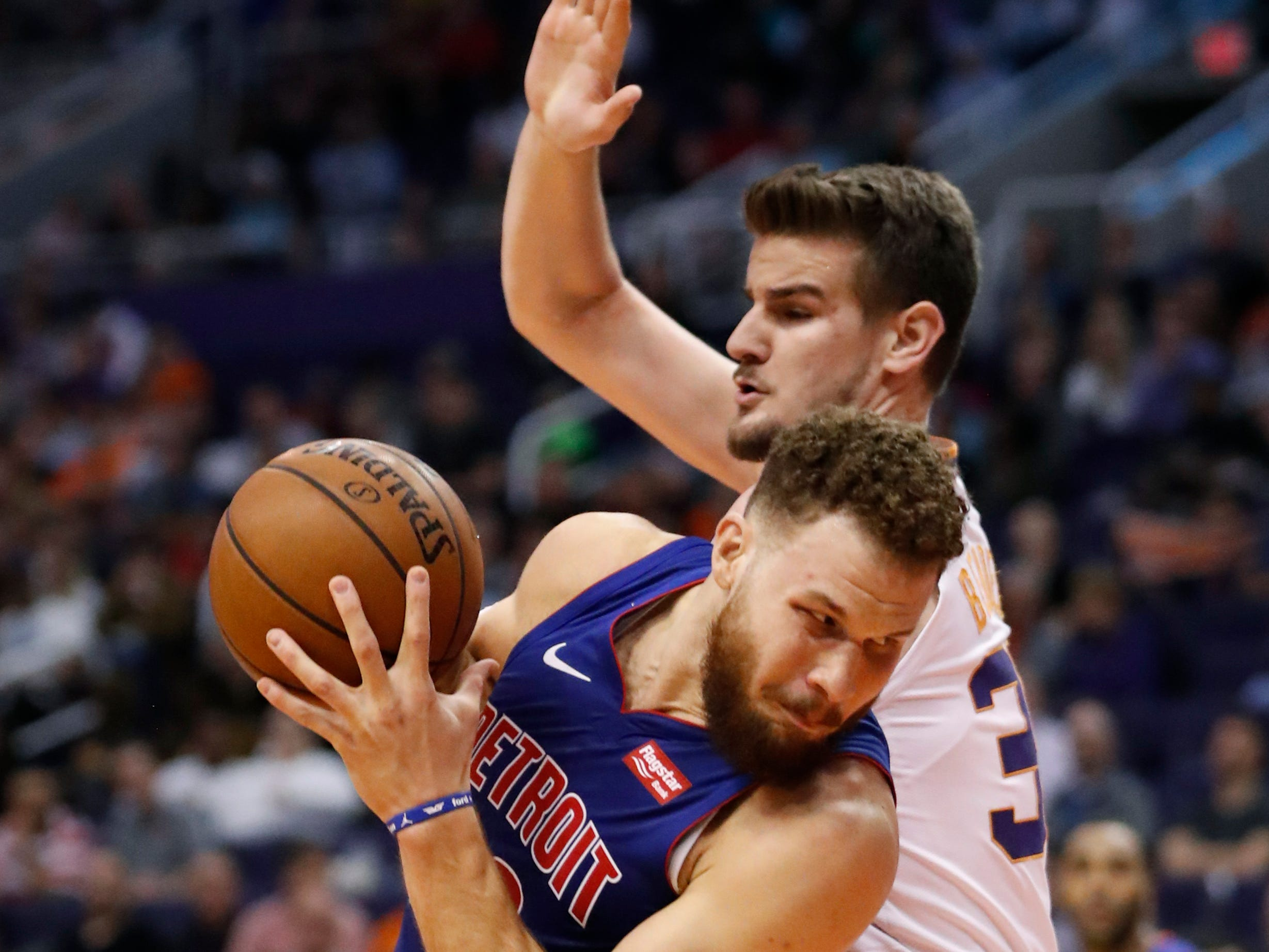 Detroit Pistons forward Blake Griffin backs down Phoenix Suns forward Dragan Bender, right, during the first half of an NBA basketball game Thursday, March 21, 2019, in Phoenix.