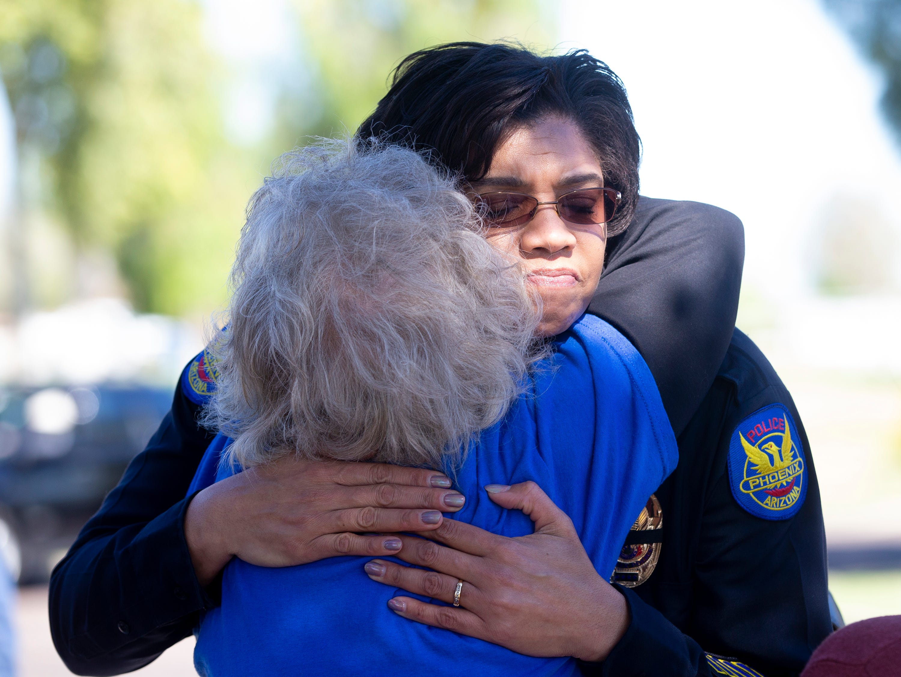 Phoenix Police Chief Jeri Williams gets a hug from Carol Hobbs March 22, 2019, before a prayer service outside Phoenix Police Maryvale Precinct for Officer Paul Rutherford, who was killed in a crash March 21.