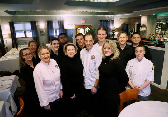 Staff from The Would Restaurant surround the management team who are front row, from left, co-owners, Claire Winslow & Debra Dooley, executive chef Fred Kormann and assistant manager Lisa Bozydaj at the restaurant in Highland on March 21, 2019.