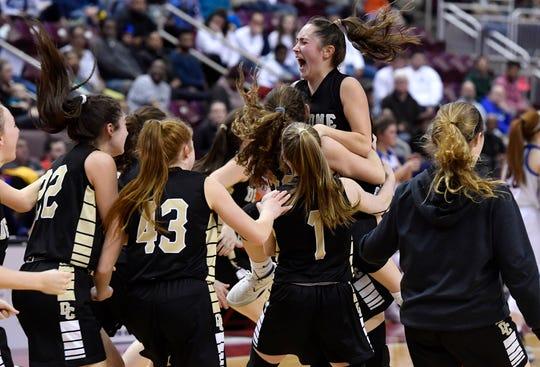 The Delone Catholic girls' basketball team celebrates after winning the PIAA Class 3-A state championship last March.