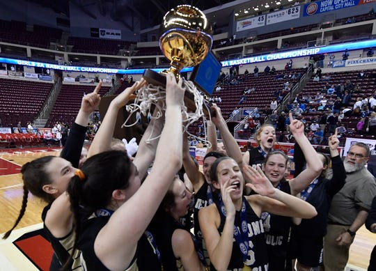 The Delone Catholic Squirettes celebrate with the PIAA Class 3-A girls' basketball championship trophy, Thursday, March 21, 2019. 