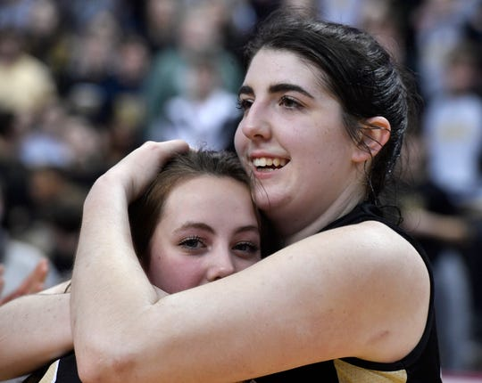 Bradi Zumbrum hugs Dee McCormick after Delone Catholic defeated Dunmore 49-43 in PIAA Class 3-A girls' basketball championship, Thursday, March 21, 2019. 