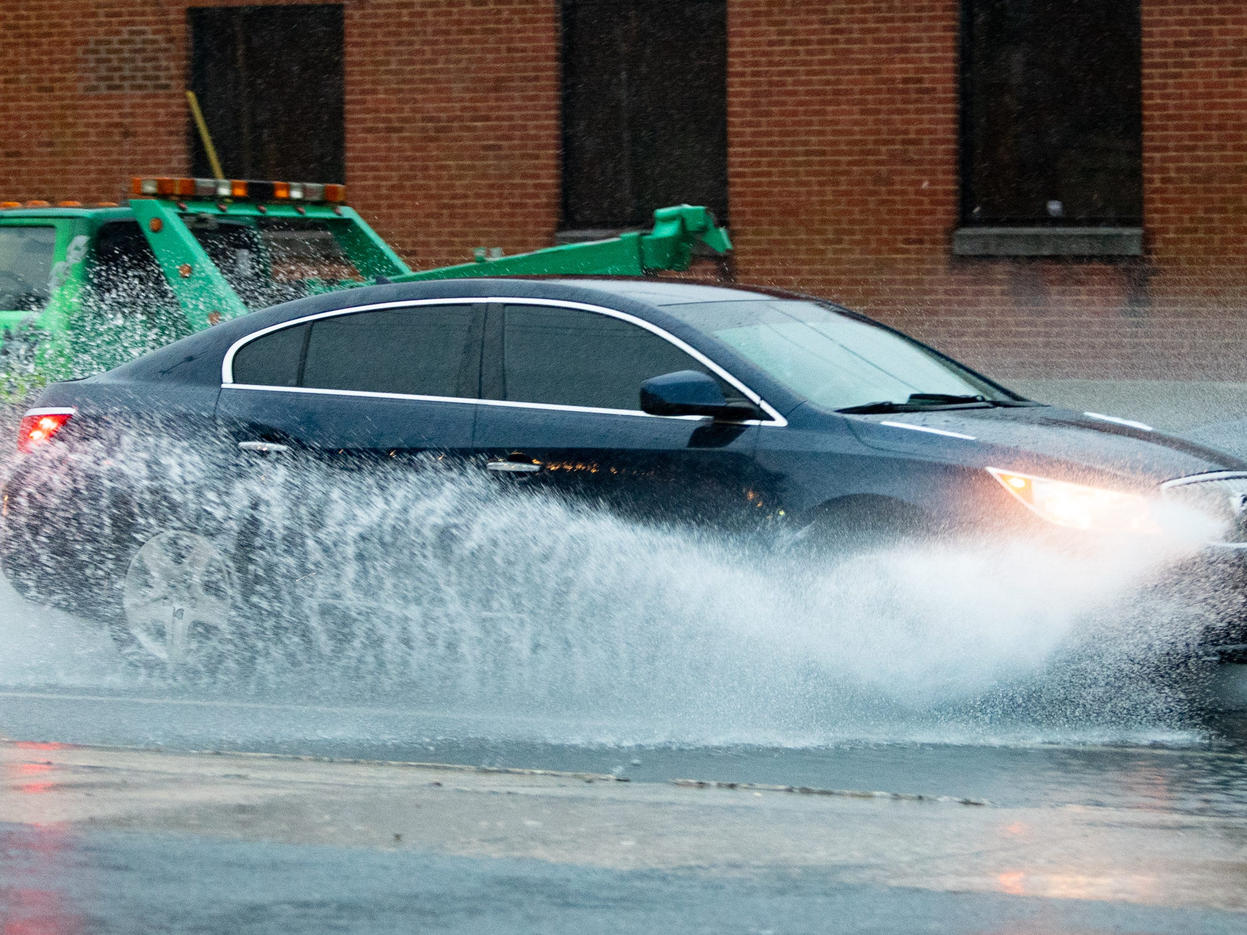 Cars spread water everywhere as they navigated the wet roads on Thursday. Rain continued through the night into Friday, forcing the closure of several flooded roads.