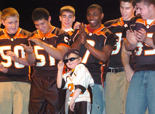 """Cancer survivor Tucker Haas, center, strikes a pose after performing a rendition of the Black Eyed Peas song  """"Boom Boom Pow"""" with the Central York High School football team Saturday April 17, 2010. Now a high school senior, Haas participated in his last mini-THON at Central York this weekend."""