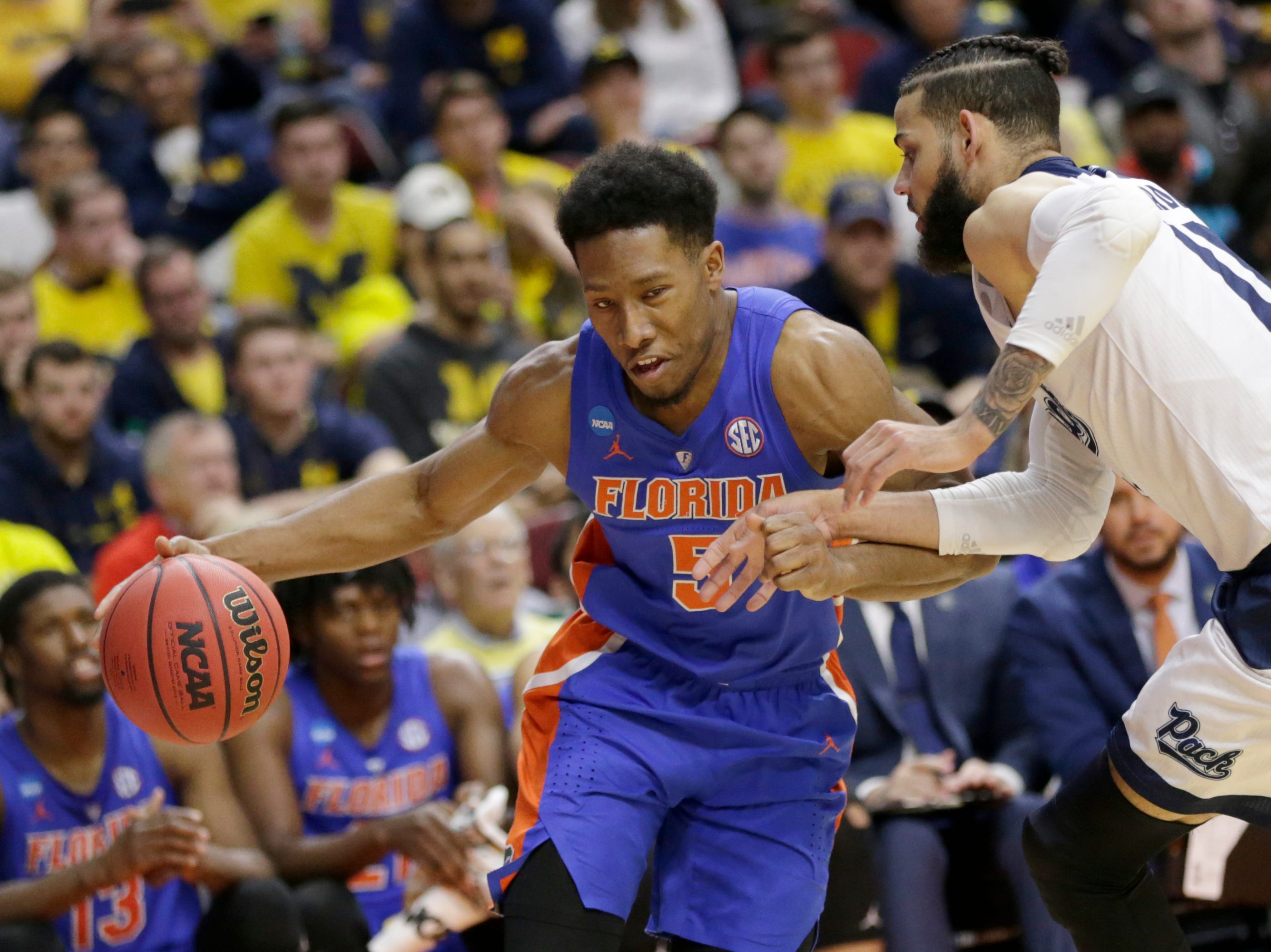 Florida's KeVaughn Allen (5) drives around Nevada's Cody Martin (11) during the second half of a first round men's college basketball game in the NCAA Tournament, in Des Moines, Iowa, Thursday, March 21, 2019. (AP Photo/Nati Harnik)