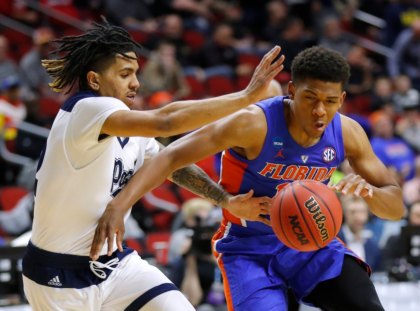 Florida guard Noah Locke drives past Nevada's Jazz Johnson, left, during Thursday's NCAA Tournament game in Des Moines.