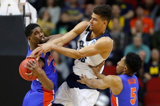 Nevada forward Trey Porter, center, fights for a rebound with Florida's Kevarrius Hayes, left, and KeVaughn Allen, right, during Thursday's game in Des Moines.