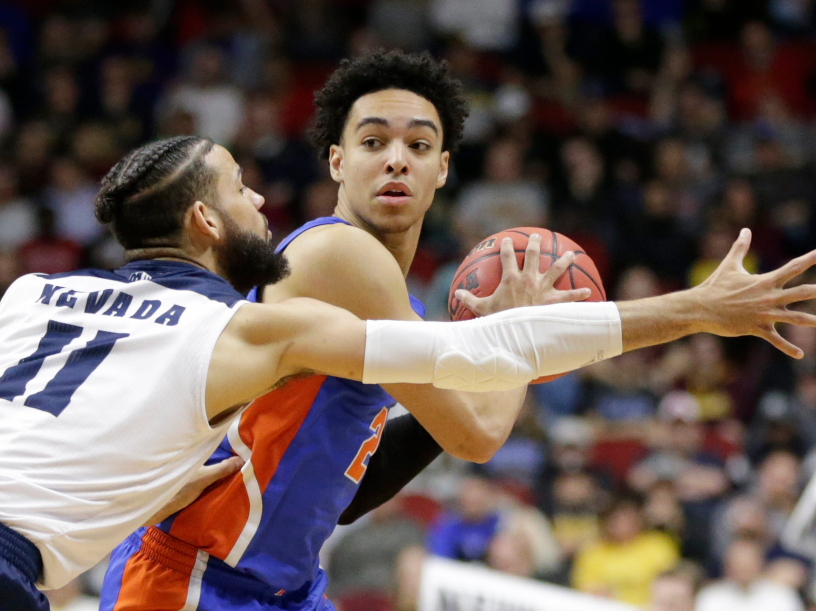 Florida's Andrew Nembhard, right, is defended by Nevada's Cody Martin (11) during the second half of a first round men's college basketball game in the NCAA Tournament in Des Moines, Iowa, Thursday, March 21, 2019. (AP Photo/Nati Harnik)