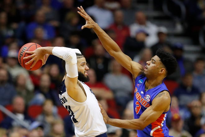 Nevada forward Cody Martin, left, passes over Florida's Jalen Hudson during Thursday's first-round game in Des Moines.