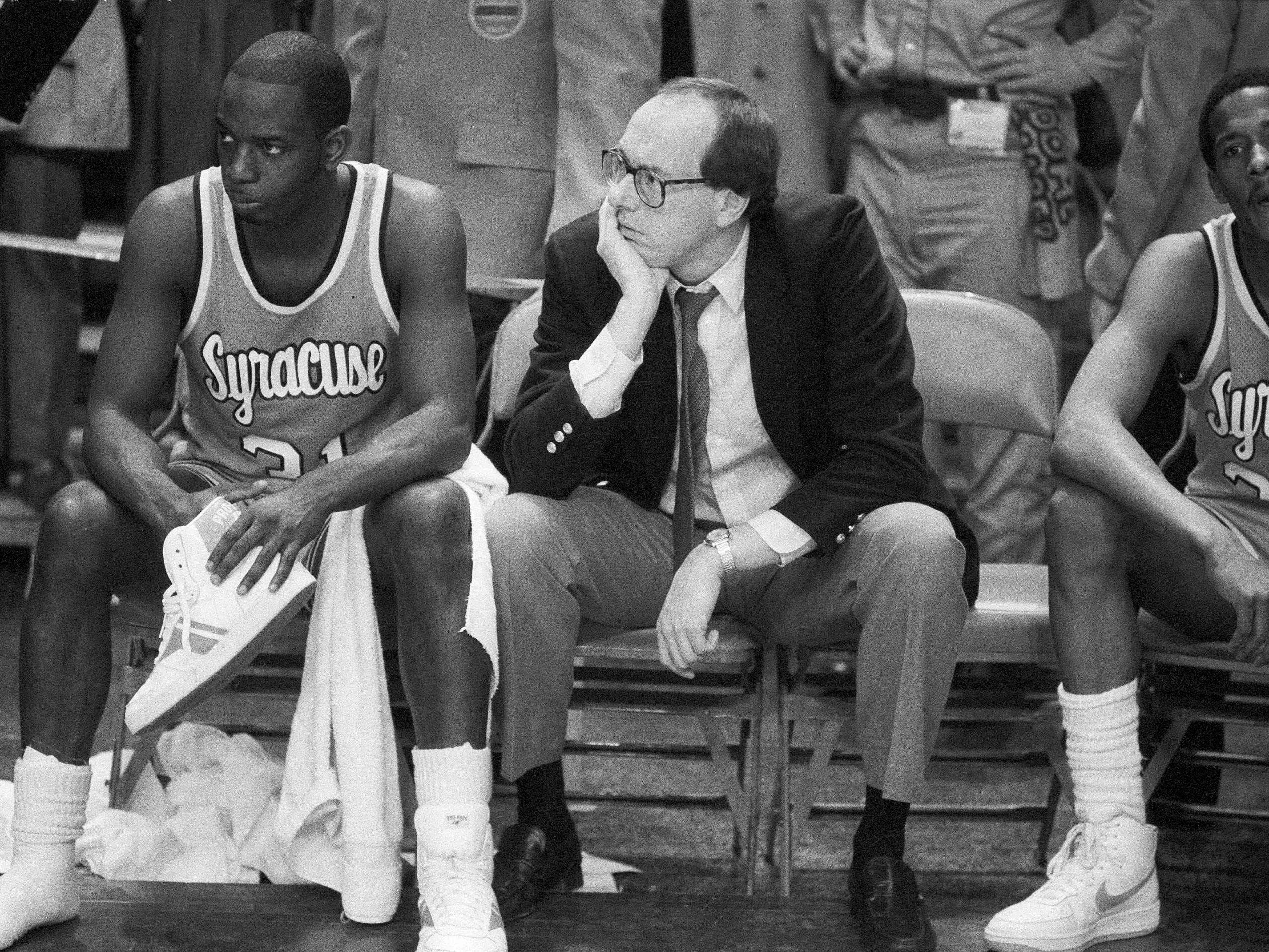 FILE - In this March 10, 1984, file photo, Syracuse coach Jim Boeheim, right, and Syracuse player Dwayne Washington (31) watch as Georgetown University took control in overtime of the Big East Conference championship basketball game at Madison Square Garden in New York.