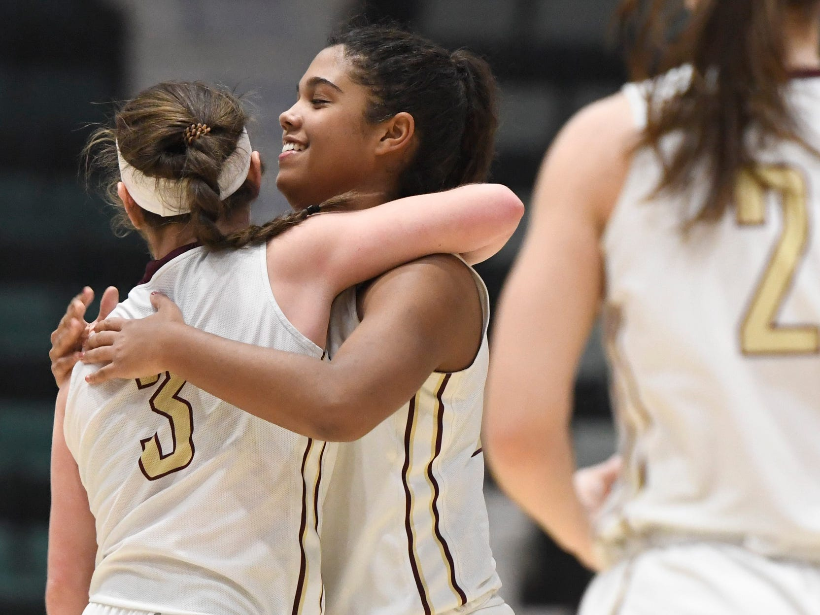 Pittsford Mendon's Ellie Mooney (3) hugs her teammate after getting a foul called against their opponents, James Madison during their Girls Class A Federation Tournament of Champions semifinal at Cool Insuring Arena on Friday, March 23, 2019, in Glens Falls, N.Y.
