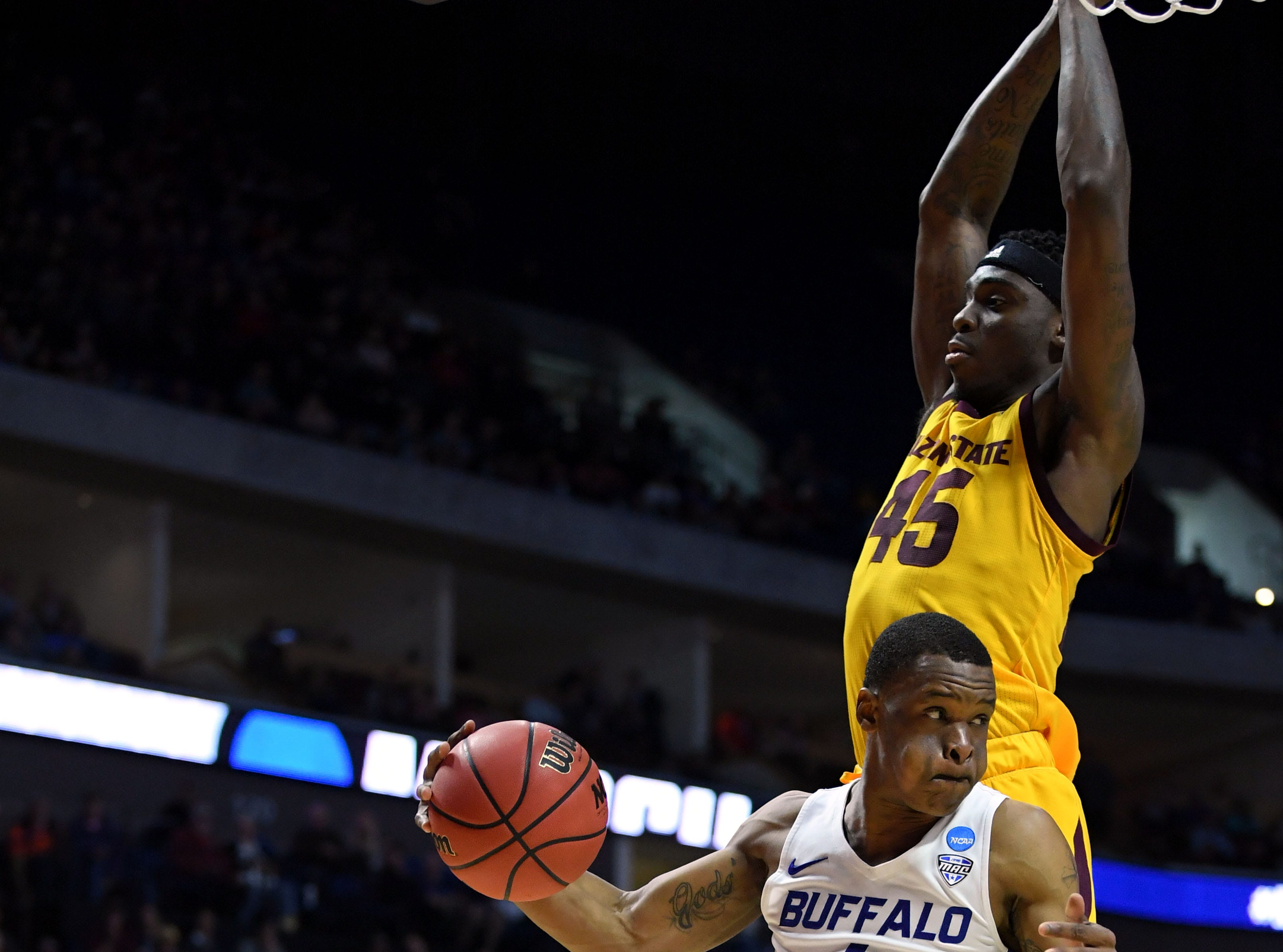TULSA, OKLAHOMA - MARCH 22:  Davonta Jordan #4 of the Buffalo Bulls drives against Kimani Lawrence #14 and Zylan Cheatham #45 of the Arizona State Sun Devils during the first half of the first round game of the 2019 NCAA Men's Basketball Tournament at BOK Center on March 22, 2019 in Tulsa, Oklahoma. (Photo by Harry How/Getty Images)